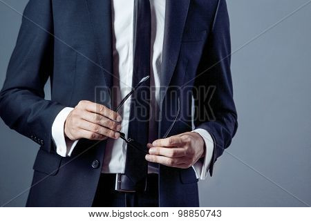 man in suit on a grey background, hands closeup