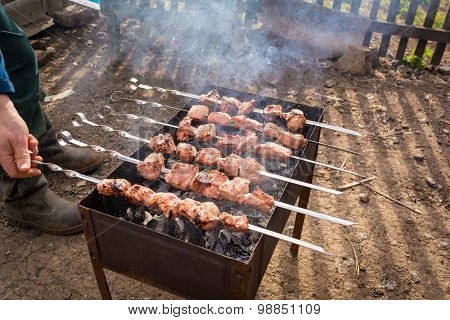 Hand turns the skewer with meat on grill