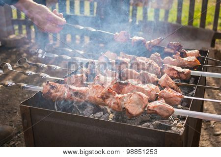Hand turns the skewer with meat in smoke on grill
