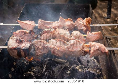 Semi-finished meat skewers on the grill in smoke