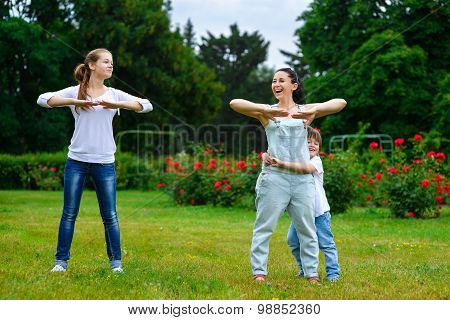 Portrait of happy family doing physical and sports exercise or fitness in park
