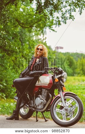 Biker girl in leather jacket on a motorcycle. Warm toned image