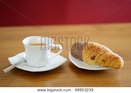 Cup of coffee and a chocolate croissant