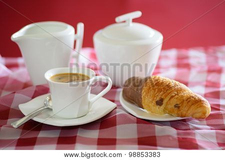 Cup of coffee, croissant, a milk jug and a sugar bowl