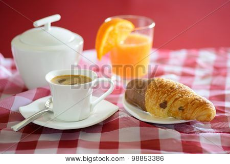 Cup of coffee, croissant, orange juice and a sugar bowl