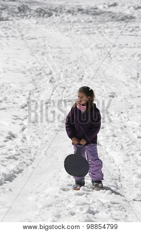 Little Girl Plays With Sledging In Winter On The Snow