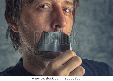 Fighting Censorship, Man Removing Duct Tape From Mouth