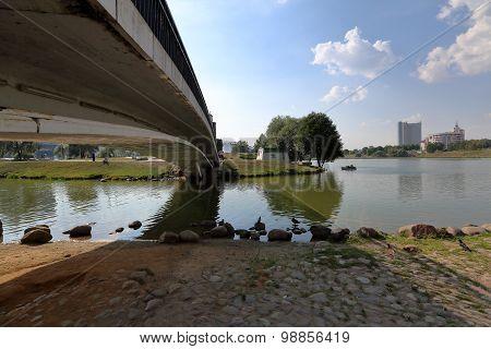 Small pedestrian concrete bridge over a narrow city river