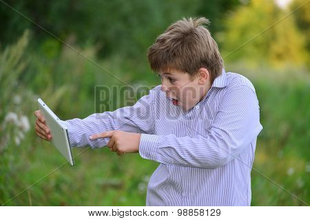 Teen Boy With  Tablet Computer At Nature