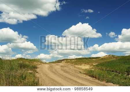 Country Road Ending In Blue Sky With Big Cumulus Clouds