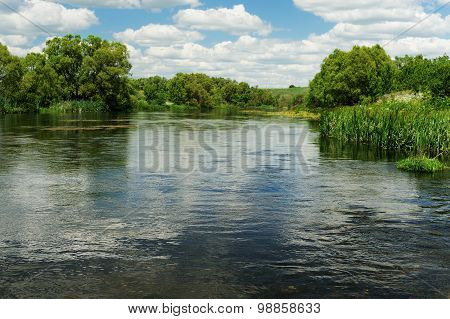 Quiet River With Green Trees On The Banks And Blue Sky With White Clouds
