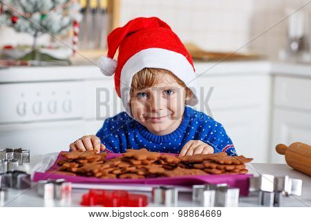 Little Boy Baking Gingerbread Cookies In Domestic Kitchen