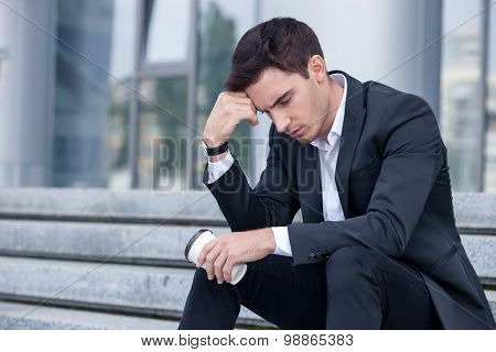 Attractive young businessman is worrying about his job