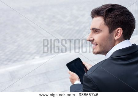Attractive young businessman is using tablet for work