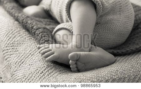 beautiful newborn baby's legs on a soft blanket. black and white