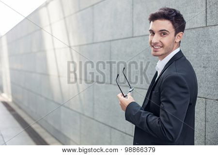 Cheerful young businessman is expressing positive emotions