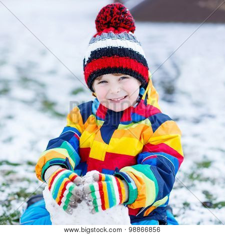 Little  Boy In Colorful Winter Clothes Playing With Snowman, Outdoors