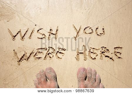 Conceptual wish you were here handwritten in sand for natural, symbol, tourism or conceptual designs background with feet