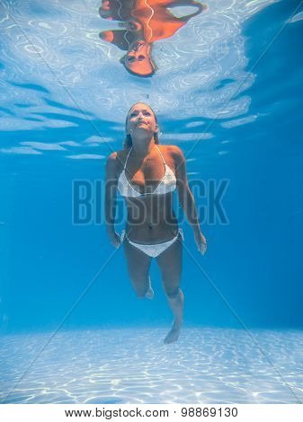 A young blonde woman diving in a blue clean water