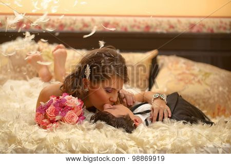 Bride And Groom Playing With Feathers Pillow Fight Bed Wedding Day