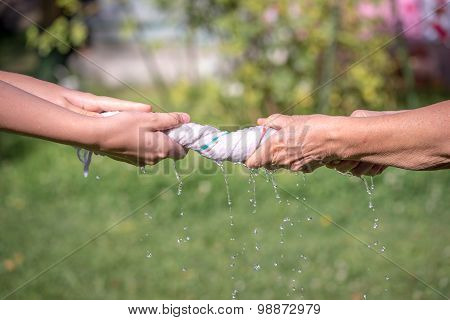 Hands Squeeze Wet Fabric On A Grass Background
