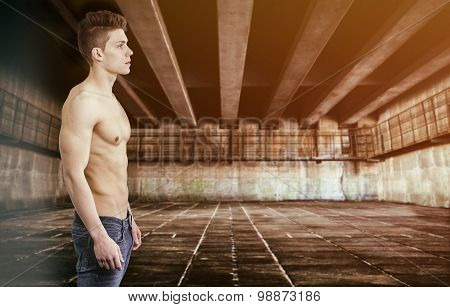 Muscular shirtless young man with jeans, indoors