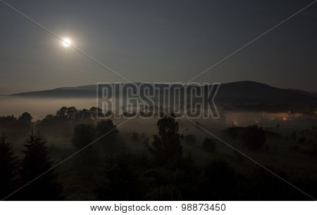 Full moon, night view of the mountains shrouded in mist