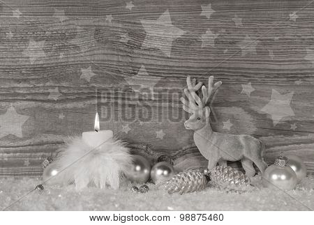 Festive Christmas decoration in grey, silver and white colors with moose and one burning candle for the first advent.