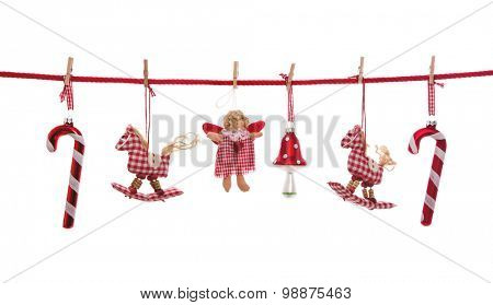 Red white checked Christmas decoration isolated on white hanging on a line with clothes pegs.