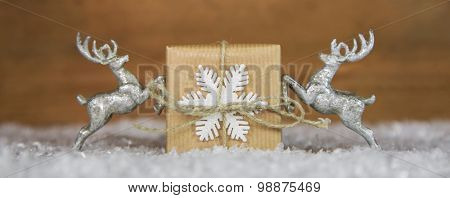 Christmas decoration with two silver reindeer holding a present.