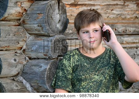 teenager boy talking on cell phone standing by  wooden wall