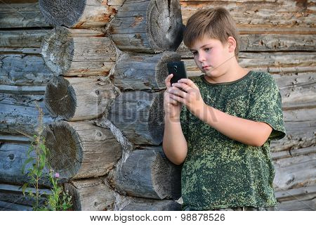 Boy teenager writes sms standing by awooden wall