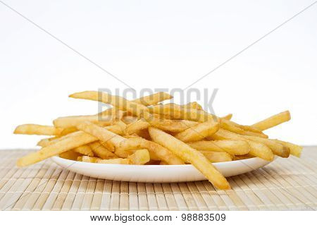 Potatoes fries in a little white paper bag on wood board