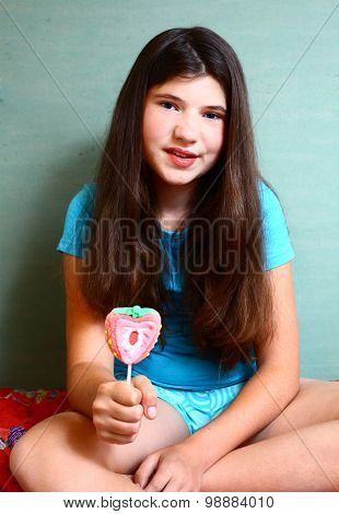 preteen beautiful girl with strawberry candy on stick