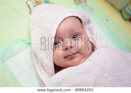 Cute baby girl covered by pink towel after bath