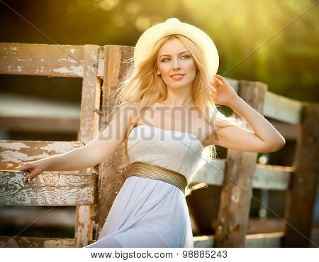 Beautiful blonde girl with country look near an old wooden fence in sunny summer day