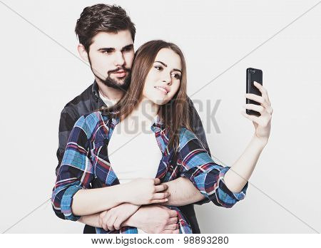 tehnology, internet, emotional  and people concept: Capturing happy moments together. Happy young loving couple making selfie and smiling while standing against white background.