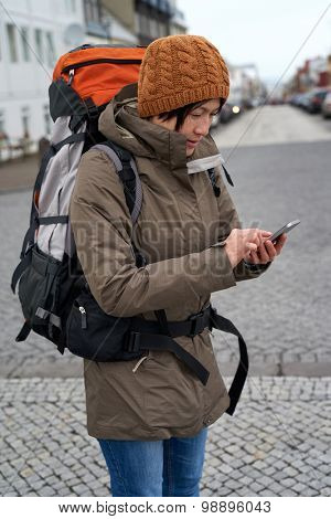 Young Asian backpacker tourist woman in rain jacket and beanie busy with her mobile Phone middle of urban city street