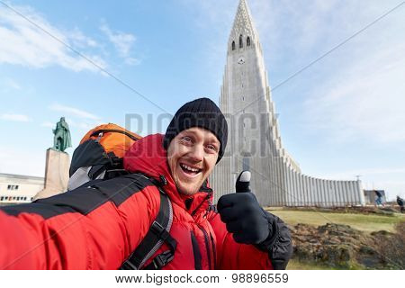 happy  Caucasian man taking travel tourist selfie with the Hallgrimskirkja cathedral in reykjavik iceland in the background