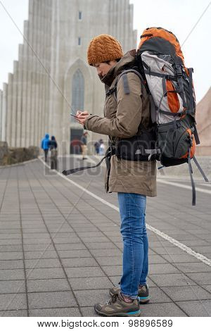 Young Asian woman in rain jacket and beanie carrying backpack busy with her mobile Phone in front of cathedral