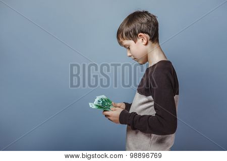 Boy teenager  European appearance  ten years  holding a wad  of