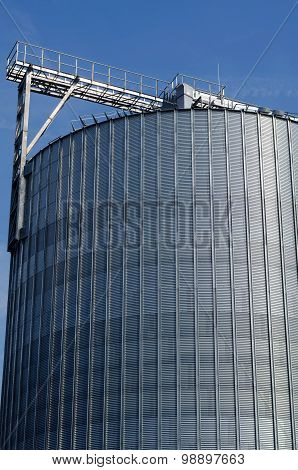 Industrial Silos In The Field Against The Blue Sky