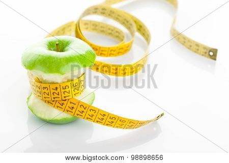 Green apple core and measuring tape