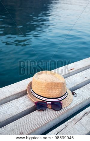 Sunglasses, flip-flops and hat on the wooden texture in summer.
