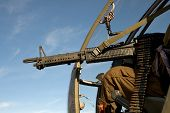 stock photo of m60  - helicopter in air with machine gun pointing out - JPG