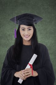 picture of graduation gown  - Happy female graduate student standing in the classroom while wearing graduation gown and holds a diploma - JPG