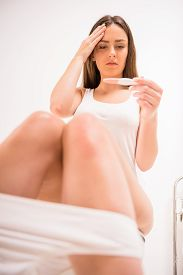 picture of pregnancy test  - Woman holding pregnancy test with two stripes - JPG