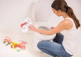 picture of vomiting  - Young woman vomiting into the toilet bowl in the early stages of pregnancy or after a night of partying and drinking - JPG