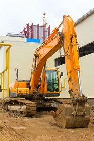 picture of backhoe  - backhoe on the background of construction of the plant - JPG