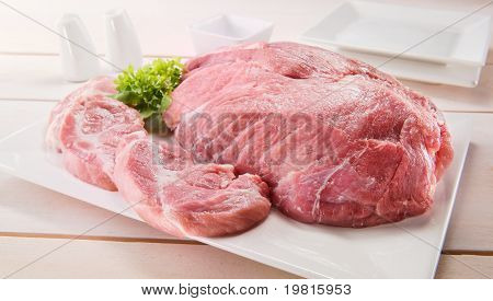 Raw chuck steak with tableware on a wooden table